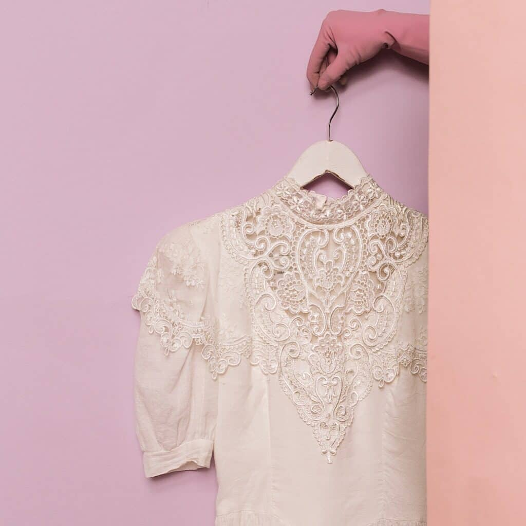 Photo shows a white blouse with lace detailing hanging on a white hanger being held by a hand wearing a pink glove against a lavender wall.