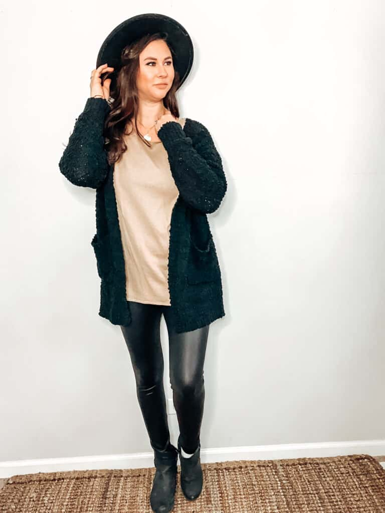 This thrifted winter outfit is made up of a camel color sweater underneath a textured knit black cardigan, paired with some black faux leggings, a black hat, a gold medallion necklace, and some black faux leather ankle boots.