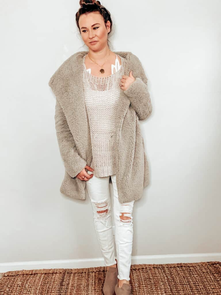 This cozy winter outfit is made up of a gray teddy style jacket, a gray open knit sweater, some white distressed skinny jeans, a gold medallion necklace, and some taupe booties.