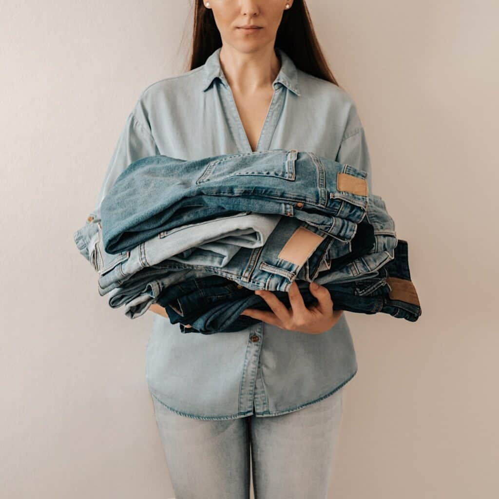 Photo shows a woman dressed in all denim holding a plie of jeans,