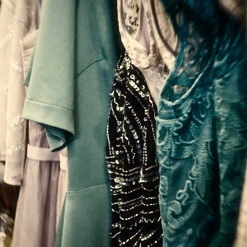 Photo shows assorted women's tops on hangers in teal, white, and black with varying materials and designs.