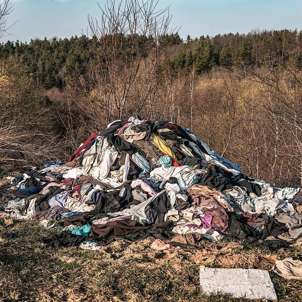 This photo of a pile of clothes that have been thrown in a landfill is a great example of what we want to avoid. one of the benefits of shopping second hand is you are saving items from being thrown into landfills.