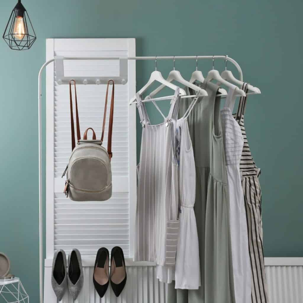 A few different style dresses in similar neutral tones hanging on a white rack along side a backpack purse and 2 sets of heels in a room with light green walls and a white door.