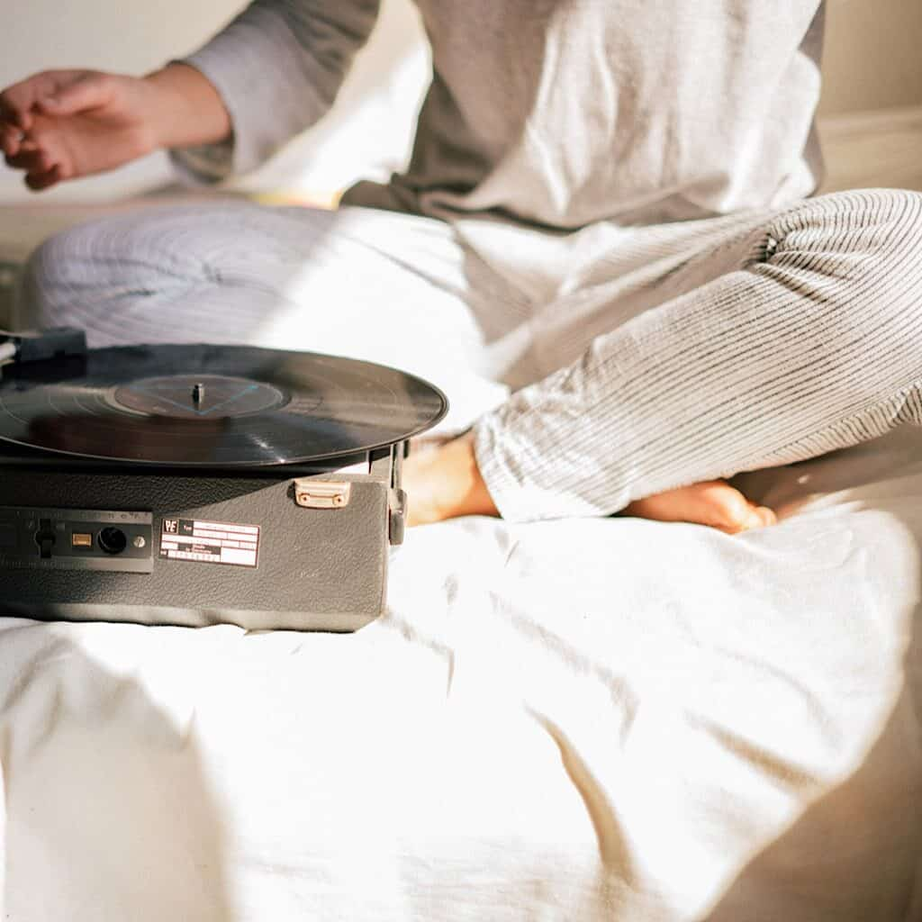 A woman sitting on a bed wearing light colored loungewear with a record player in front of her.