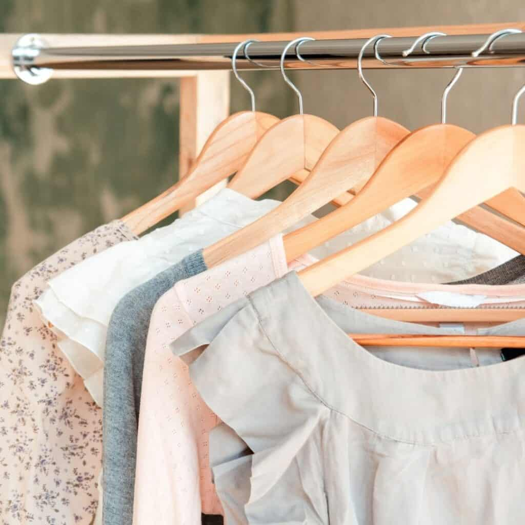 Different style tops in blush pinks and light blues hanging on a rack.