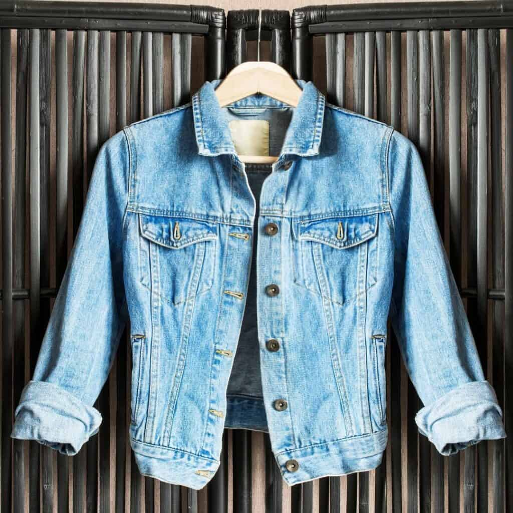 A denim jacket hanging on a black bamboo partition.