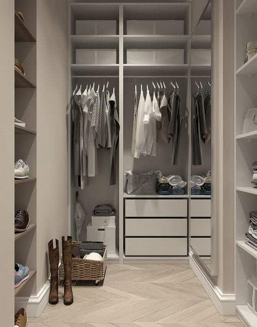 A white walk in closet with a small wardrobe in neutral tones hanging on the bar, some items are folded on shelves and there are shoes on the side wall on shelves.