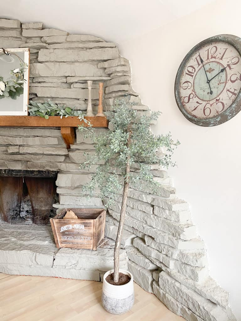 Check out how to make a fake tree for your own home that looks super realistic. Photo shows an artificial potted tree in front of a stone fireplace with a wooden box on the ledge. There is a clock on the wall, and on the fireplace mantel there is a window mirror with a spring hoop wreath on it, a garland, and 2 wooden antique looking candle holders.