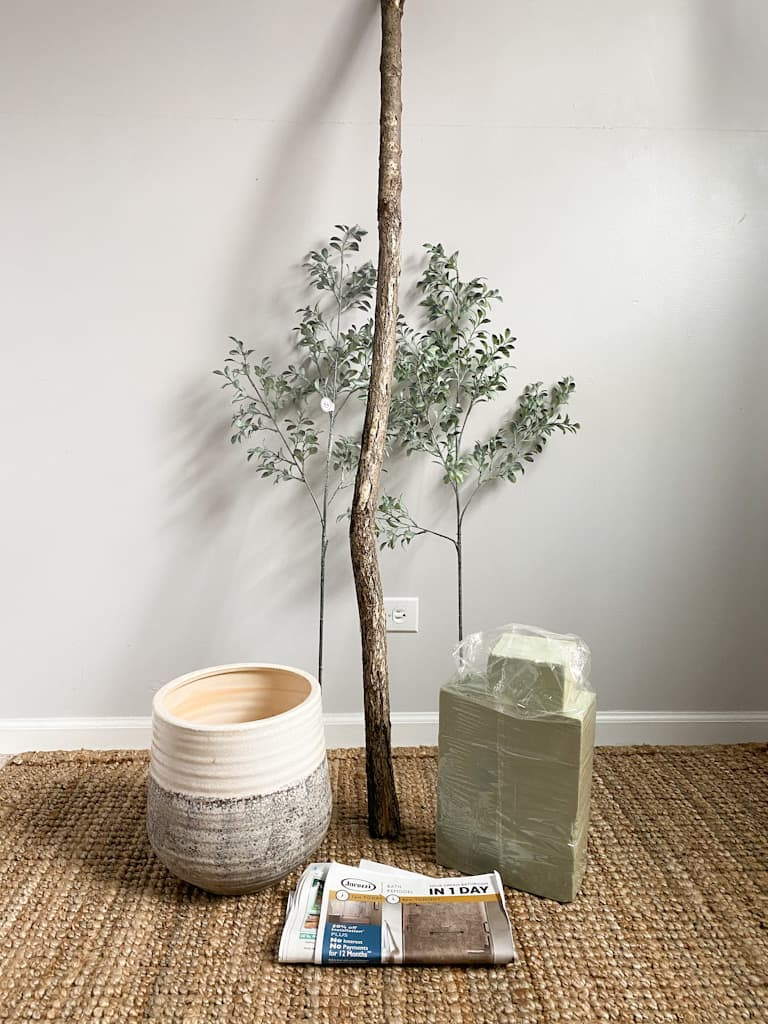 Some of the supplies you will need to make a fake tree including, a tree branch, some fake greenery stems, blocks of floral foam, and some recycled newspaper.