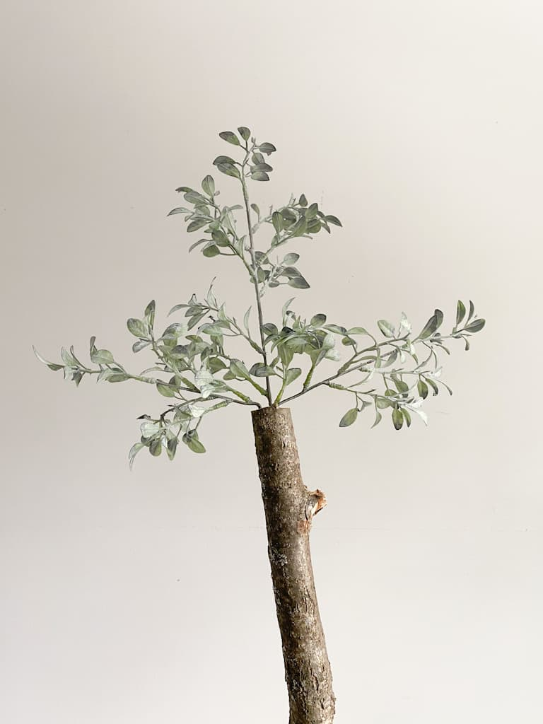 The top 3 branches that form the top of the fake tree, sticking out of the top of a real tree branch used as the trunk of the fake tree.