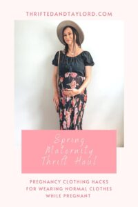 A pregnant woman wearing a black eyelet cropped shirt, a black maxi skirt with pink and purple flowers on it, a gray wide brim hat, a straw bag, gold necklaces, and taupe ankle boots. These are both maternity second hand clothes that are actually regular clothes you can wear while pregnant.